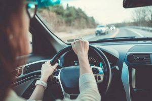 Femme les mains sur le volant d'une voiture en train de rouler
