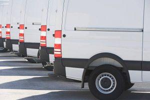 Plusieurs camionnettes blanches sur un parking