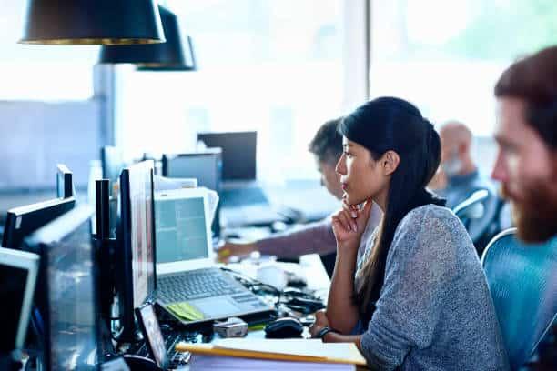 Employés devant des écrans d'ordinateur dans un open space