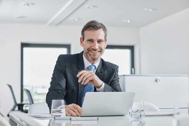 Homme d'affaires souriant derrière son bureau de travail