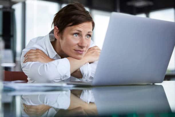 Femme appuyée devant écran d'ordinateur
