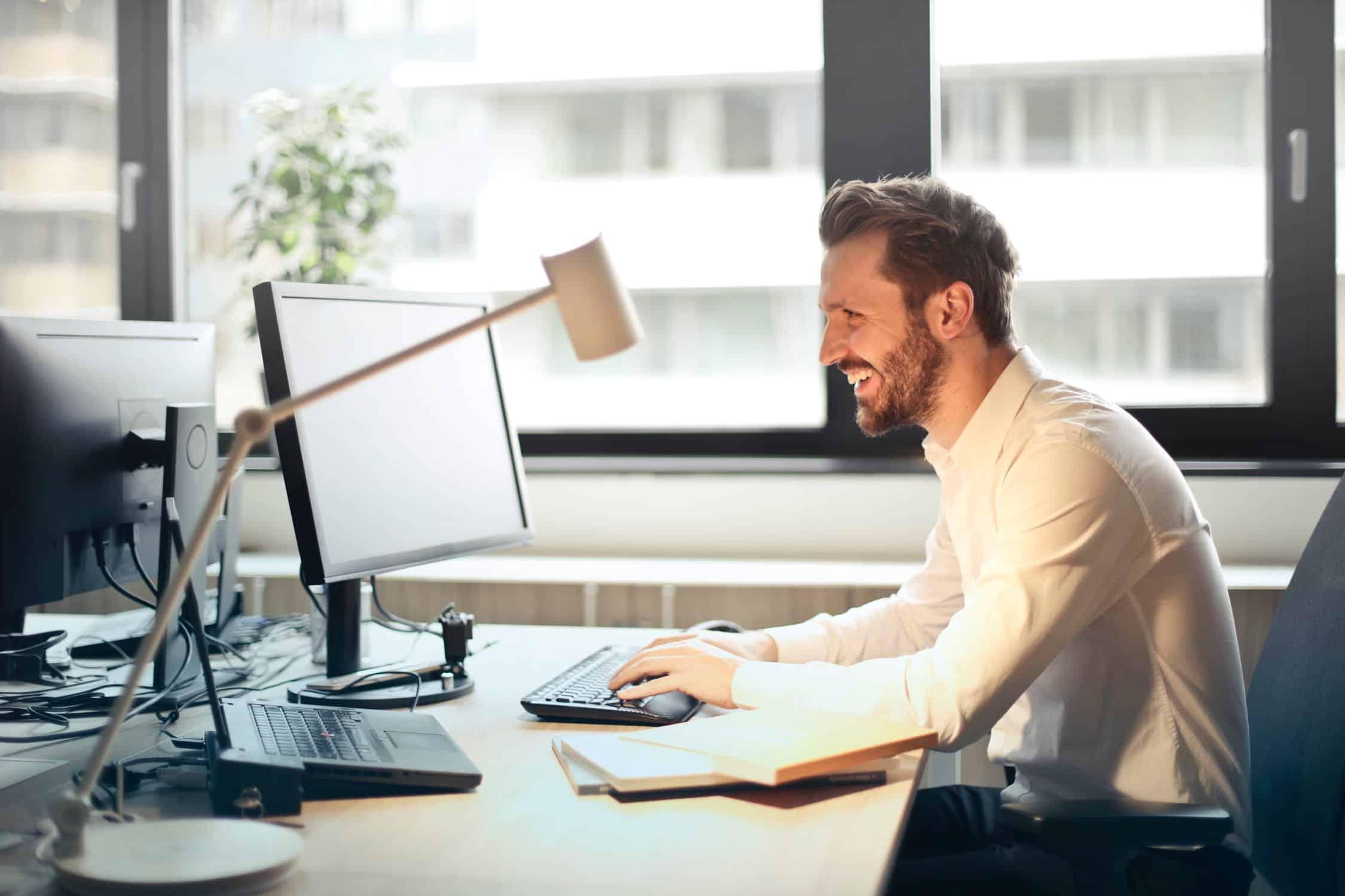 Salarié motivé par son travail qui sourit devant son bureau