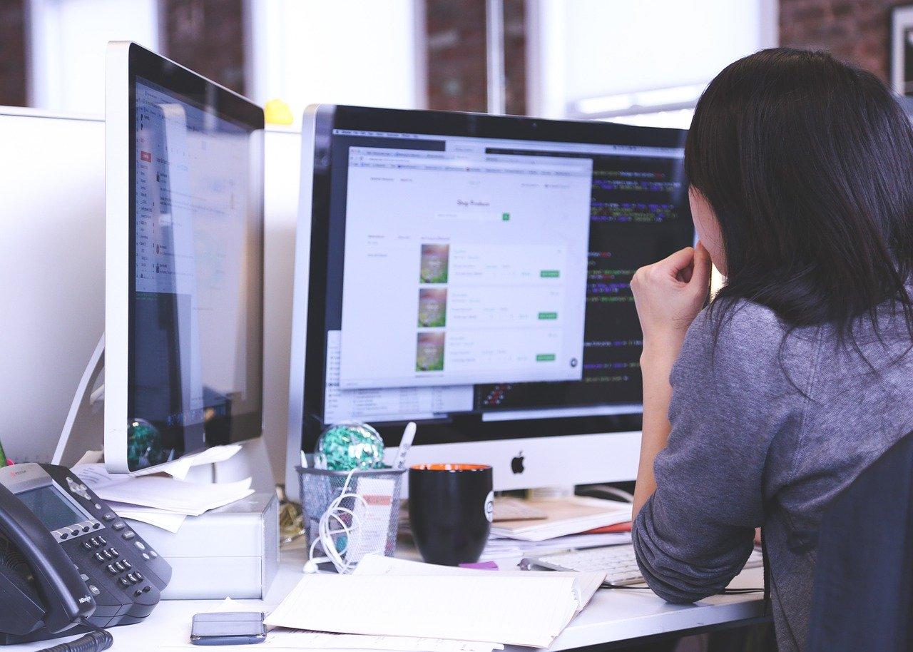 jeune femme qui travaille sur deux écrans d'ordinateur