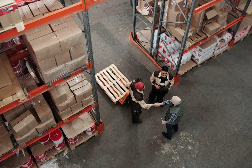 trois personnes qui se saluent dans un entrepôt